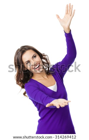 Happy smiling beautiful young woman carring, holding or showing something transparent or visual imaginary, in violet casual clothing, isolated over white background - stock photo