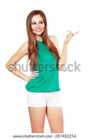 Happy smiling beautiful young woman pointing copyspace or something, isolated over white background - stock photo