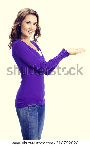 Happy smiling beautiful young woman showing copyspace or something, in violet casual clothing - stock photo