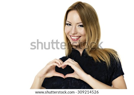 Happy smiling beautiful young woman showing heart symbol gesture, isolated over white background - stock photo