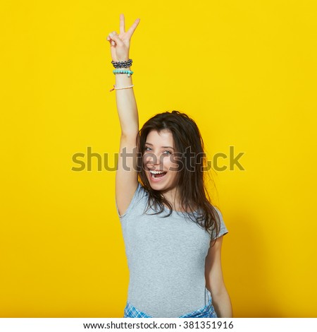 Happy smiling beautiful young woman showing two fingers or victory gesture, isolated over yellow background - stock photo