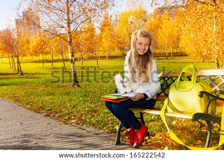 Happy smiling blond teen girl with long hair holding coffee and books and papers with bag laying on the bench, in autumn park - stock photo