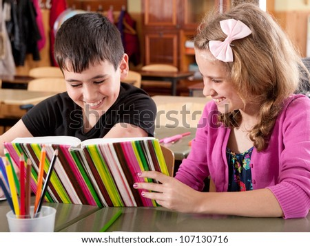 Happy smiling boy and girl reading book at school during a lesson - stock photo