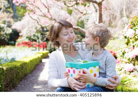 happy smiling boy holding gift for his young beautiful mother for mother's day celebration in the park - stock photo