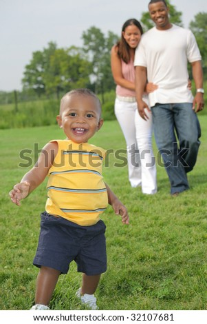 Happy Smiling Boy Playing Outdoor with Parents In Summer Sunny Day, Focus on Boy - stock photo