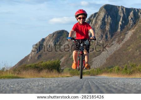 Happy smiling boy riding a bicycle. Andoya, Norway. Summer shot - stock photo