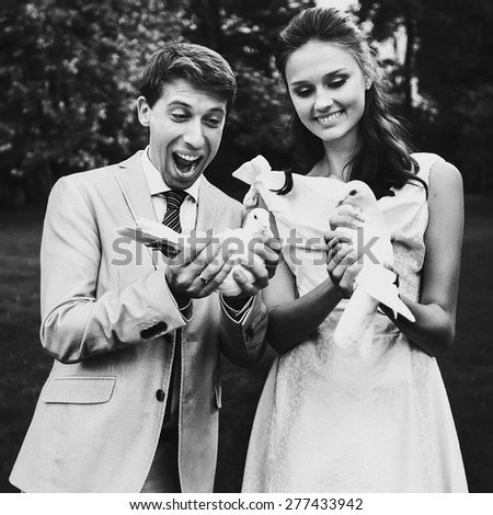 Happy smiling bride and groom holding white doves on a sunny day