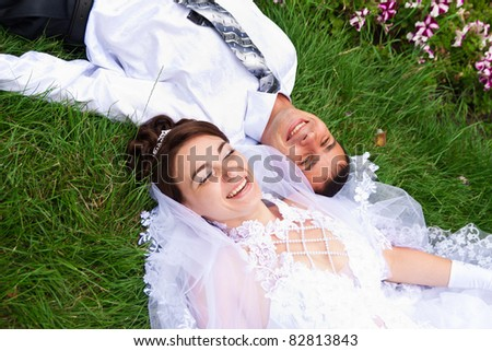 Happy smiling bride and groom  lying on a green grass laughing