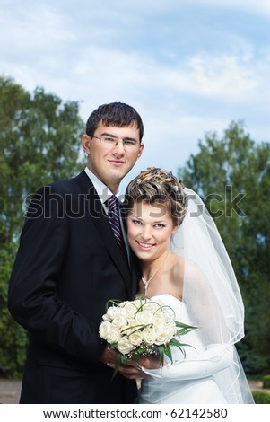 Happy smiling bride with groom outdoors against blurred trees and blue sky