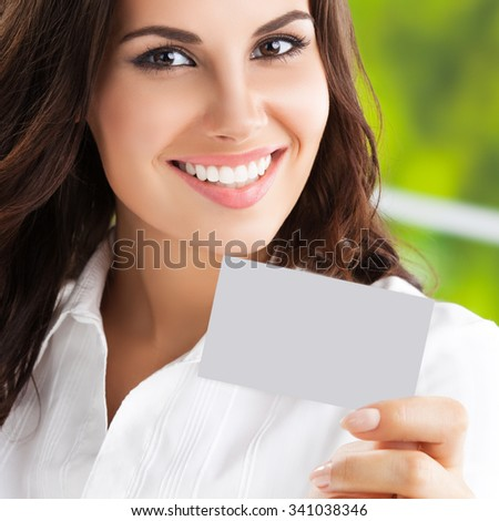 Happy smiling brunette businesswoman showing blank business or plastic card with copyspace area for slogan or text. Invitation concept. - stock photo