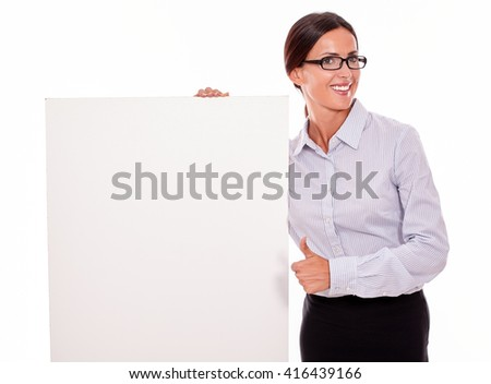 Happy smiling brunette businesswoman with glasses looking at the camera, holding a placard with her toothy smile, wearing her straight hair tied back and a button down shirt, with a thumb up gesture - stock photo