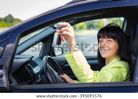 Happy smiling brunette woman 35 years old with car key in hand sitting In The Driver's Seat of Her Car with spring-summer mood. Woman Driving. Dressed in green jacket with sun glasses on head - stock photo