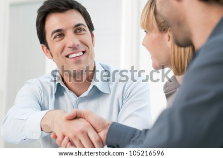Happy smiling business man shaking hands after a deal in office - stock photo