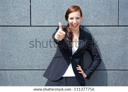 Happy smiling business woman in city holding her thumbs up - stock photo