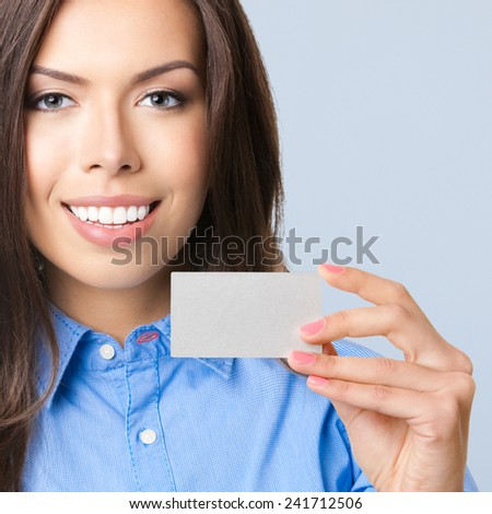 Happy smiling business woman showing blank business or credit card, against grey backround - stock photo