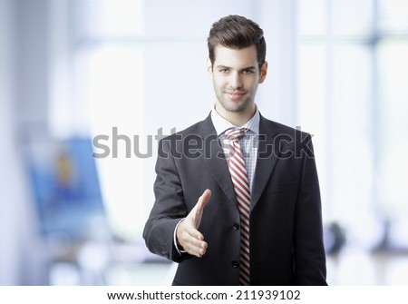 Happy smiling businessman giving hand for an handshake at office. Business people. - stock photo