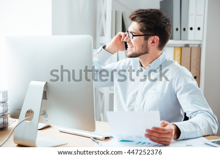 Happy smiling businessman holding documents and talking on mobile phone in the office - stock photo