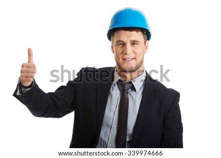 Happy smiling businessman in hard hat with thumbs up gesture. - stock photo