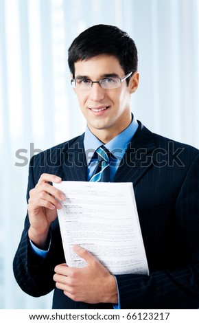 Happy smiling businessman showing document or contract, at office - stock photo