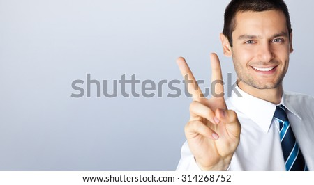 Happy smiling businessman showing two fingers, or victory gesture, posing at studio, against grey background, with blank copyspace area for slogan or text message - stock photo