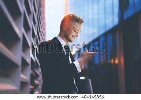 Happy smiling businessman wearing black suit and using modern smartphone near office at early morning, successful employer to make a deal while standing near skyscraper office at night, flare light - stock photo
