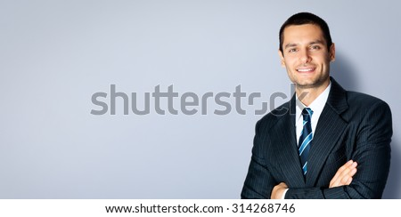 Happy smiling businessman with crossed arms pose, posing at studio, against grey background, with copyspace area for slogan or text message - stock photo