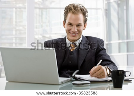 Happy smiling businessman working on laptop computer at desk.