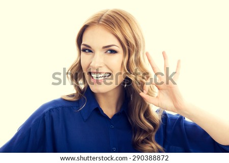 Happy smiling businesswoman in blue clothing showing okay hand sign gesture - stock photo