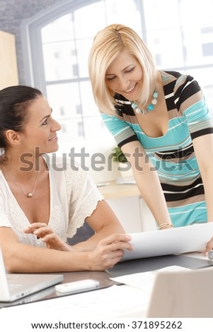 Happy, smiling casual caucasian brunette and blonde businesswomen sharing a successful work report at office desk. Paperwork. - stock photo