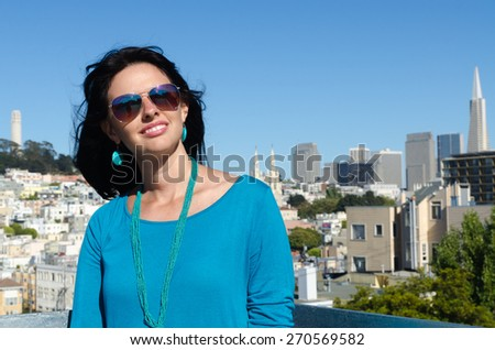 Happy smiling Caucasian brunette with iconic San Francisco cityscape on background - stock photo