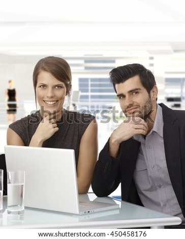Happy smiling caucasian businessman and businesswomen with laptop computer, sitting at office desk, hand under chin, looking at camera.