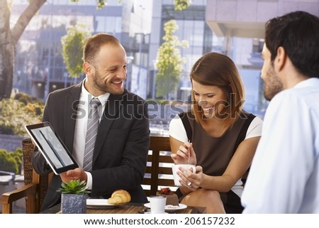 Happy smiling caucasian businessman doing presentation to colleagues at breakfast with tablet computer, outdoor. - stock photo