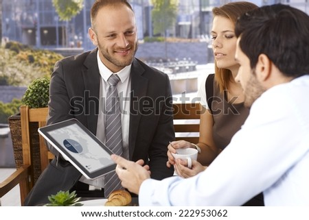Happy smiling caucasian businessman doing presentation to office workers with tablet computer, outdoor. Suit and tie. - stock photo