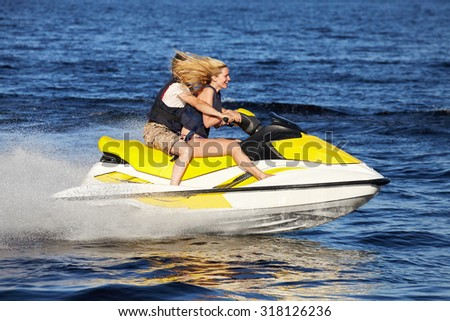 Happy smiling caucasian couple riding jet ski - stock photo