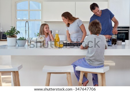 happy smiling caucasian family in the kitchen preparing breakfast - stock photo
