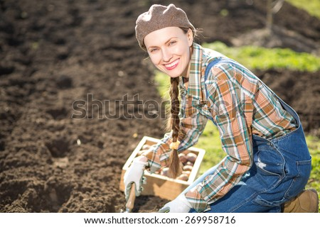 Happy smiling caucasian female farmer or gardener in a hat holding potato going to plant. Agriculture - food production, home grown food concept, copy space - stock photo