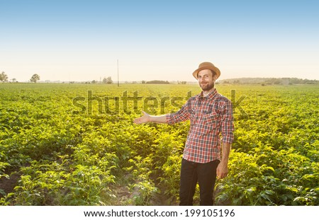 Happy smiling caucasian forty years old farmer in a hat standing proud in front of potatoes field landscape - agriculture. Layout with free text space. - stock photo