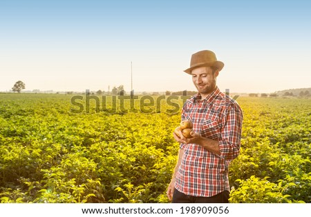 Happy smiling caucasian forty years old farmer in a hat standing proud outdoor in front of field landscape holding potatoes in hand - agriculture. - stock photo