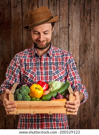 Happy smiling caucasian forty years old farmer or gardener in a hat holding wooden box of fresh vegetables on rustic vintage planked wood background. Agriculture - food production, harvest. - stock photo