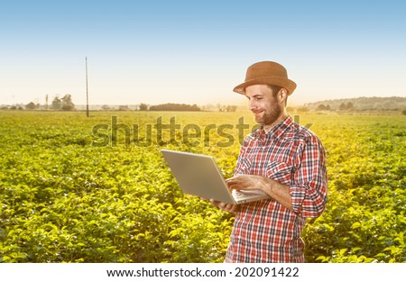 Happy smiling caucasian forty years old modern farmer in a hat standing outdoor in front of field landscape and working on laptop computer - agriculture. Layout with free text space. - stock photo