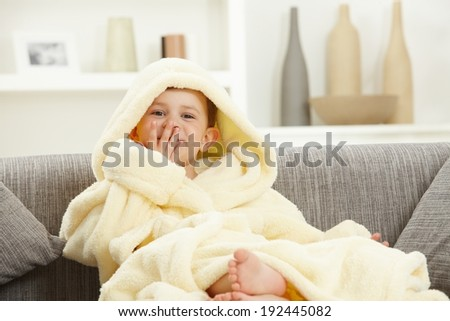 Happy smiling caucasian kid sitting in oversized bathrobe at home sofa, bare feet. Indoor, relaxed. Hood over head. - stock photo
