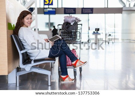 Happy smiling Caucasian woman with devices sitting in airport lounge - stock photo