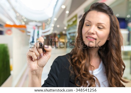 Happy smiling cheerful beautiful young business woman writing or drawing something on screen or transparent glass, by blue marker - stock photo