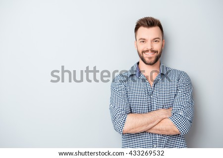 Happy smiling cheerful guy with crossed hands on gray background - stock photo