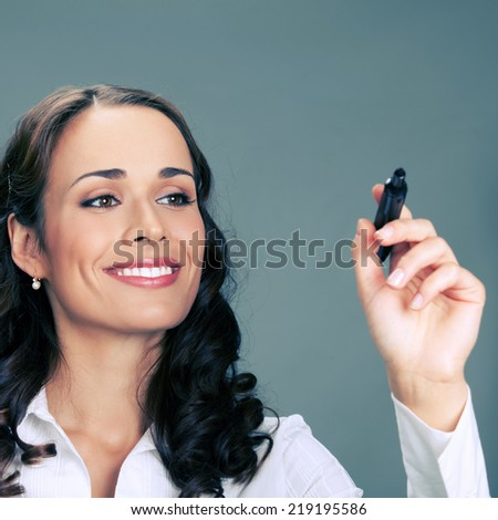 Happy smiling cheerful young business woman writing or drawing something on screen with red marker, over gray background - stock photo