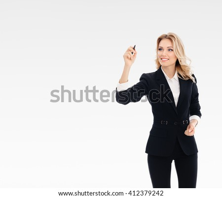 Happy smiling cheerful young businesswoman writing or drawing something on screen or transparent glass, by blue marker, on grey background, with blank copyspace area for text or slogan