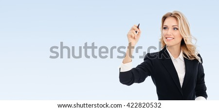 Happy smiling cheerful young businesswoman writing or drawing something on screen or transparent glass, by blue marker, on blue background, with blank copyspace area for text or slogan - stock photo