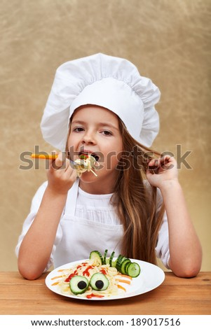 Happy smiling chef child eating a creative spaghetti dish - stock photo