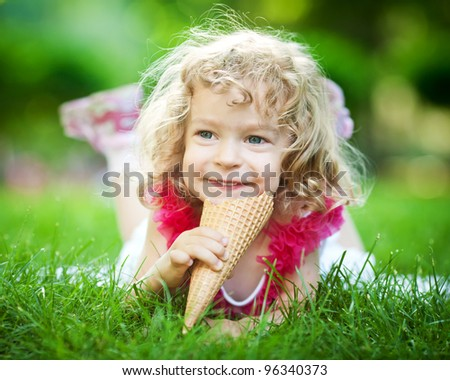 Happy smiling child eating ice-cream on green grass outdoors in spring park - stock photo