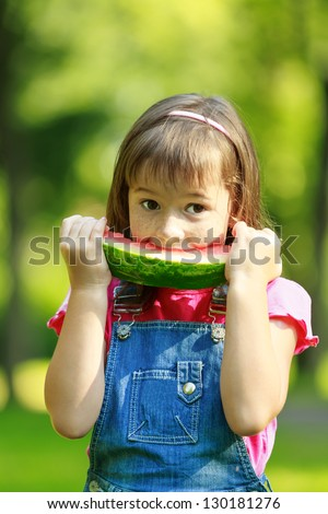 Happy smiling child eating watermelon in park